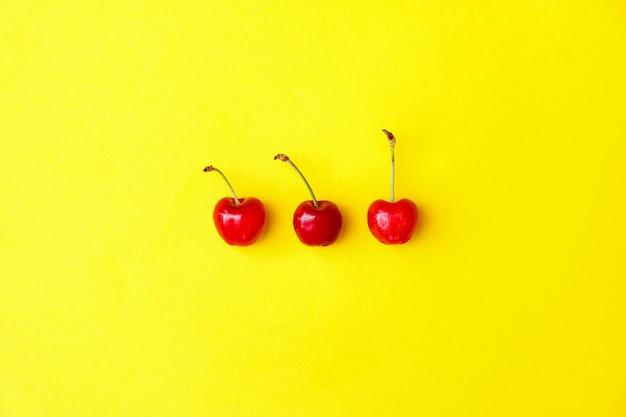 Três cerejas vermelhas frescas sobre fundo amarelo, propaganda, cartaz.