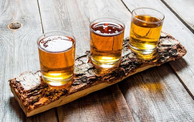 Três cervejas em um carrinho de bétula. em uma mesa de madeira.