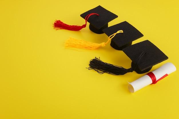 Três chapéus acadêmicos com diploma em tema de formatura de fundo amarelo