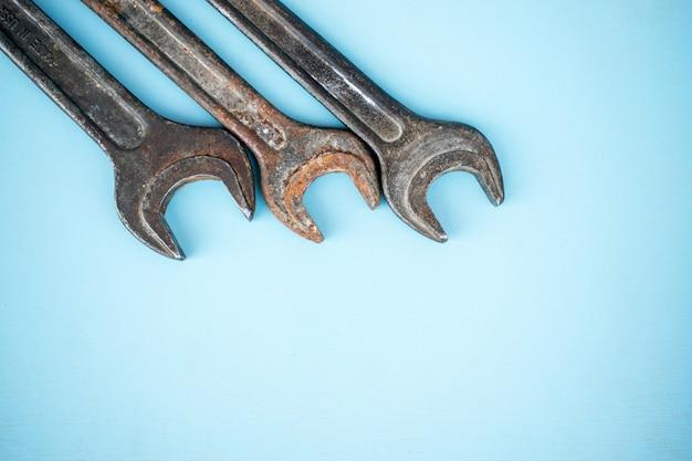 Três chaves inglesas oxidadas velhas no fundo azul. equipamentos de oficina.