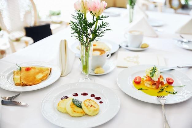 Três cheesecakes e panquecas em um prato branco com fundo de geléia de um vaso com flores restaurante
