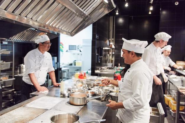 Três chefs na forma, na cozinha, preparando comida usando talheres
