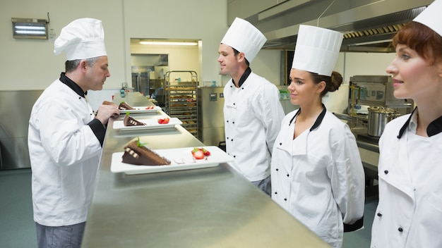 Três chefs que apresentam seus pratos para o chefe de cozinha