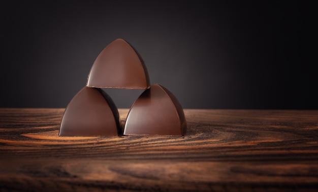 Três chocolates empilhados em uma superfície de madeira,