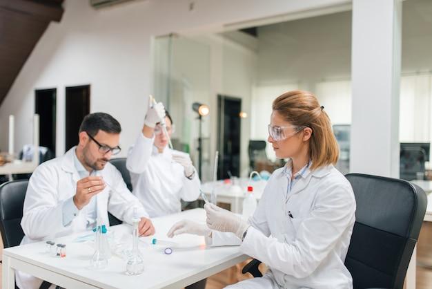 Três cientistas trabalhando. teste de qualidade da água.