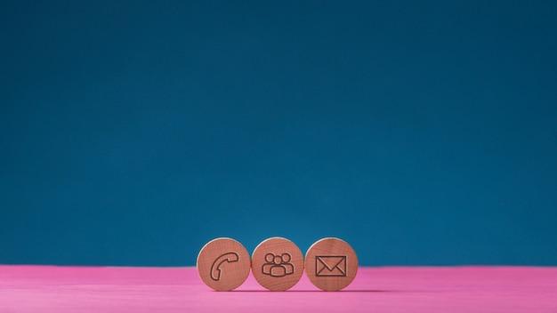 Três círculos de corte de madeira com ícones de contato e comunicação