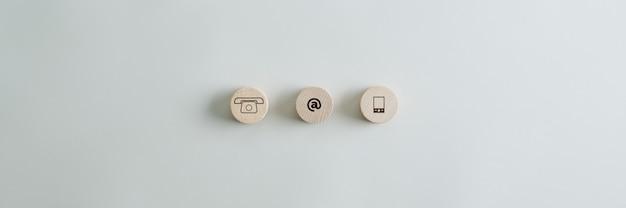 Três círculos de madeira com ícones de contato e comunicação