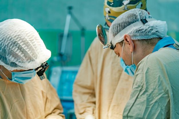 Três cirurgiões em vestidos médicos brancos e em máscaras executam a operação do paciente.