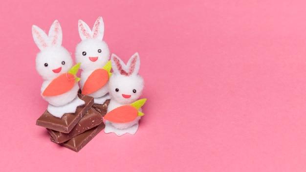 Três coelhos brancos com cenoura em pedaços de chocolate sobre o fundo rosa