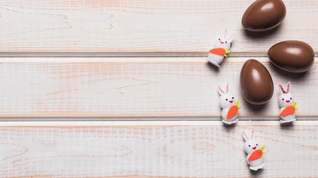 Três coelhos brancos de páscoa e ovos de chocolate na mesa de madeira