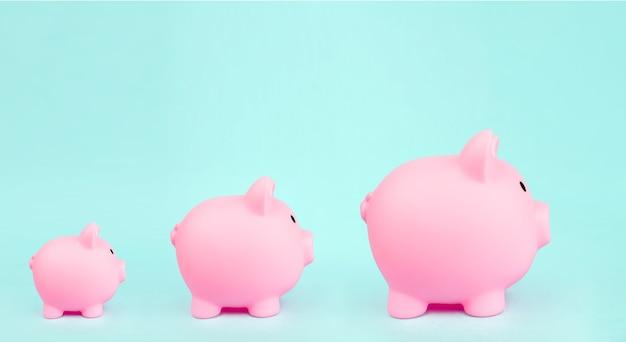 Três cofrinho rosa sobre fundo azul. conceito de crescimento financeiro.