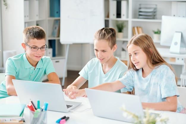 Três colegas de escola apontando para algo curioso na tela do laptop enquanto discutem o assunto em sala de aula
