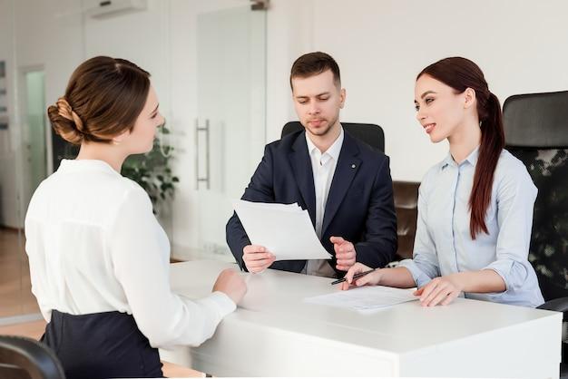 Três colegas de trabalho discutindo negócios no escritório