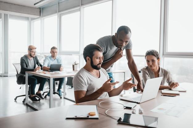 Três colegas de trabalho discutindo projetos no interior de um escritório moderno