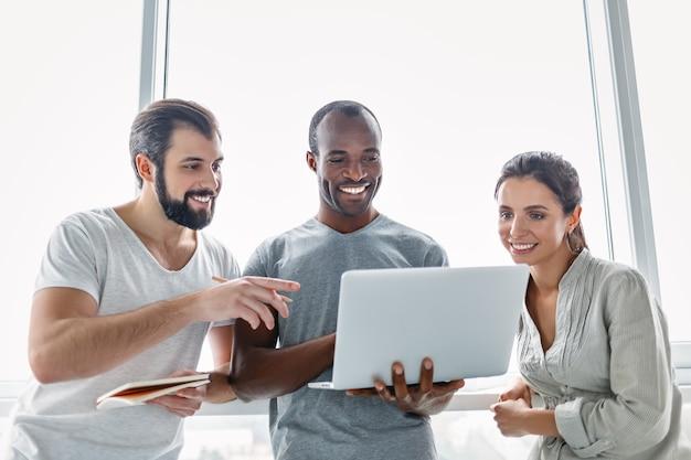 Três colegas de trabalho sorridentes em pé no interior de um escritório moderno, olhando para a tela