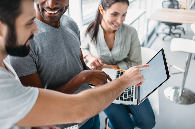 Três colegas de trabalho sorridentes falando no interior de um escritório moderno, olhando para a tela