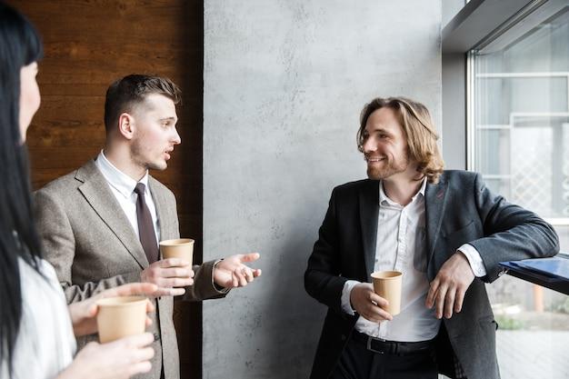 Três colegas estão conversando em um intervalo para café