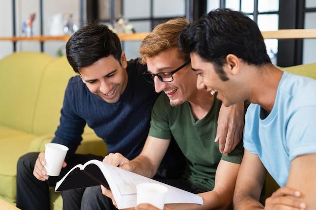 Três colegas estudantes lendo livros didáticos, rindo e bebendo