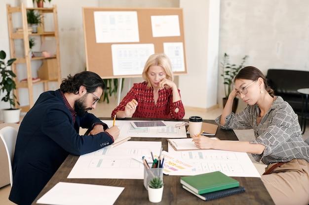 Três colegas pensativos sentados à mesa e brainstorming enquanto trabalham individualmente em um ambiente de escritório contra um quadro com esboços