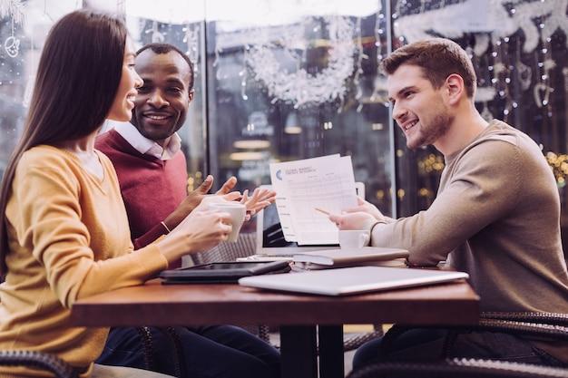 Três colegas profissionais sentados em um café enquanto conversam sobre o plano de negócios e sorrindo