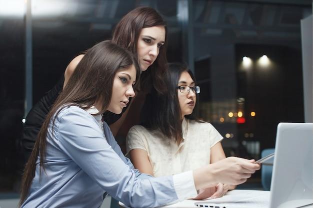 Três colegas são mulheres de negócios sentadas em uma mesa com um laptop em um escritório noturno e olhando gráficos em folhas de papel