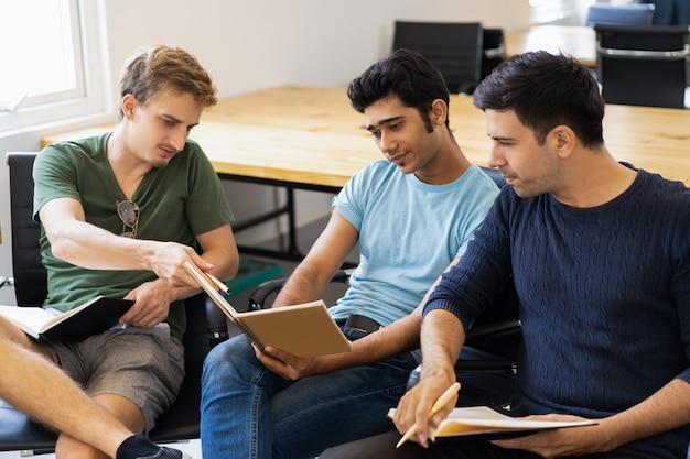 Três colegas sérios estudando, lendo livros didáticos