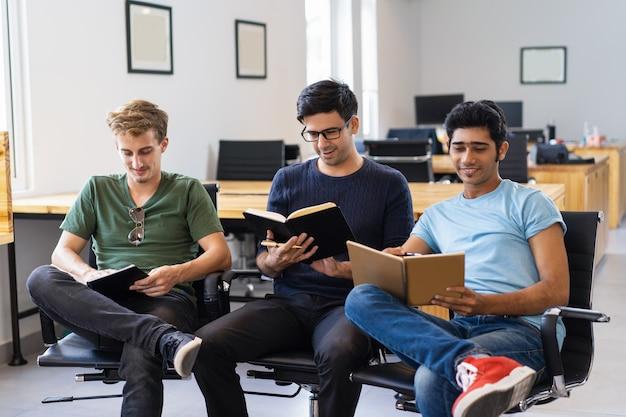 Três colegas sorridentes estudando e lendo livros didáticos