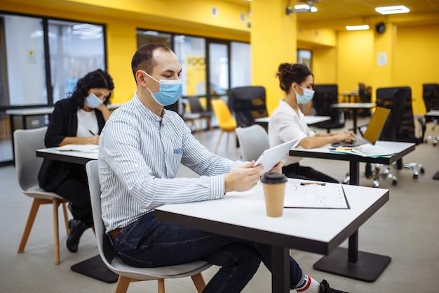 Três colegas trabalham juntos em um escritório, mantendo distância social, tecendo máscaras médicas.