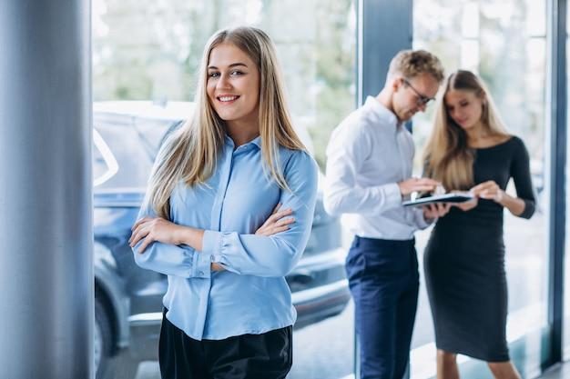 Três colegas trabalhando em um showroom de carros