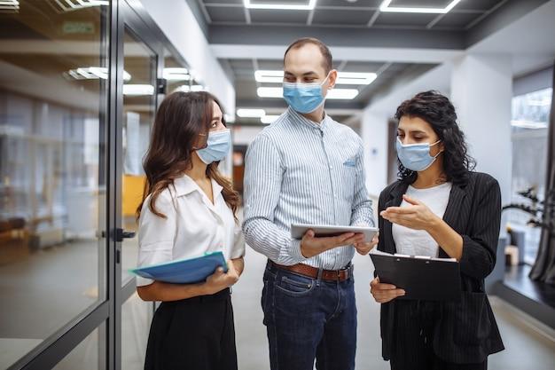 Três colegas usando máscaras médicas discutem negócios no corredor do escritório durante a quarentena de pandemia de coronavírus.