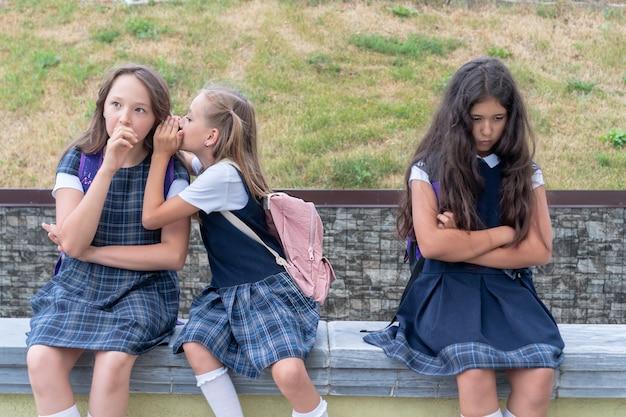 Três colegiais estão sentadas no pátio da escola