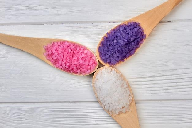 Três colheres de pau com sal colorido de cor diferente