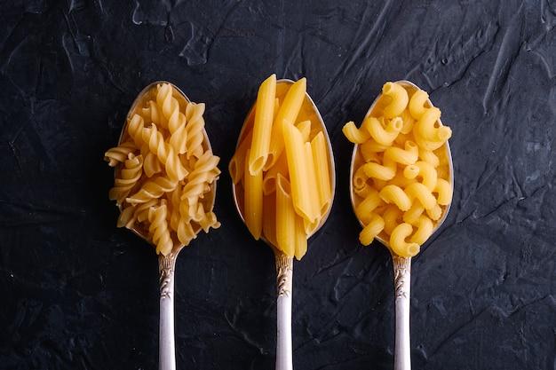 Três colheres de talheres com variedade de macarrão de trigo dourado cru na mesa texturizada preto escuro, vista superior