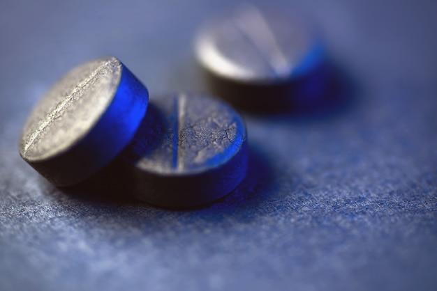 Três comprimidos de carvão ativado preto. sobre um fundo preto há luz azul no lado