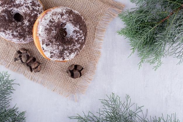 Três cones de cipreste e dois donuts em um pedaço de pano entre galhos de pinheiro em fundo branco.