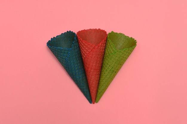 Três cones de sorvete de bolacha multi-coloridas mentem sobre um fundo rosa