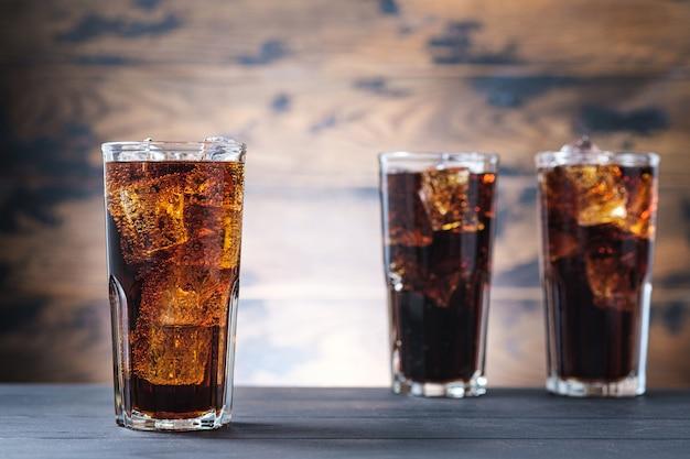 Três copos com cola e cubos de gelo