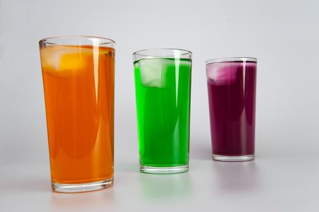 Três copos com sucos diferentes com gelo branco