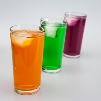Três copos com sucos diferentes com gelo