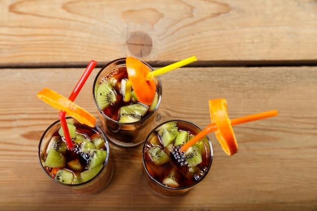 Três copos com um coquetel de frutas sobre uma mesa de madeira