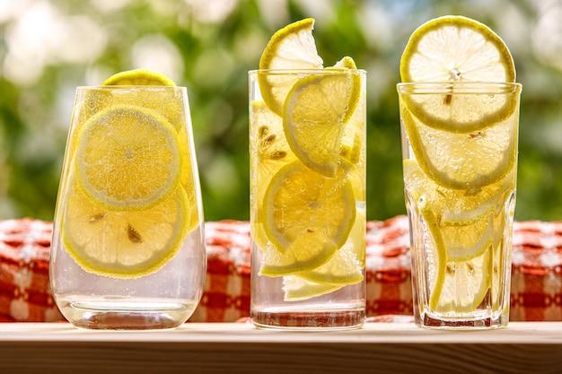 Três copos de água com limão no jardim ensolarado