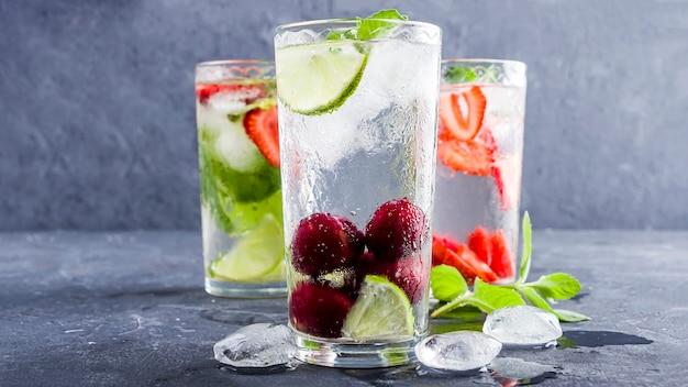 Três copos de bebida desintoxicante fresca refrescante com morango, limão, cereja e hortelã sobre fundo azul.