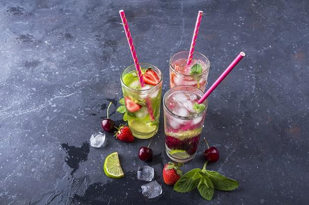 Três copos de bebida desintoxicante refrescante com morango, limão, cereja e hortelã