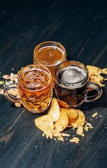 Três copos de cerveja artesanal cara, clássicos e não filtrados e escuros em um copo em cima da mesa com um lanche de batatas e nachos de amendoim e pistache
