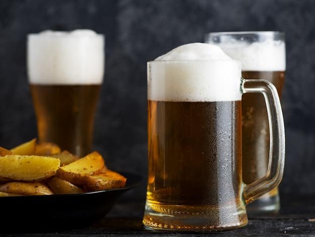 Três copos de cerveja light e batatas do país em uma mesa escura