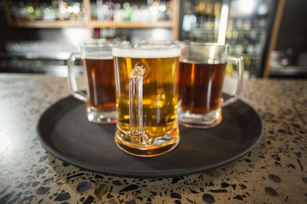 Três copos de cerveja