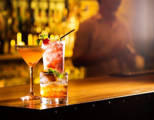 Três copos de cocktail servem na mesa de bar