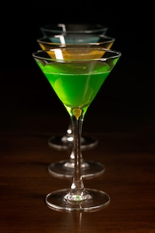 Três copos de cocktails coloridos