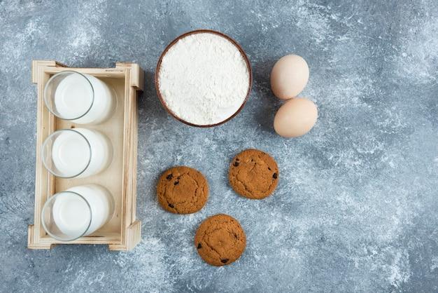 Três copos de leite com farinha e ovos em uma mesa cinza.