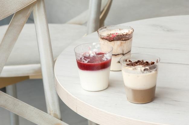 Três copos de plástico com um coquetel na mesa redonda e cadeiras